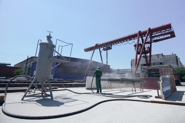 Fabrik zur reinigung von metall durch sandstrahlen. ein mann reinigt ein metallprofil sandstrahlen