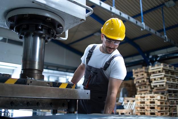 Fabrikangestellter, der an industrieller bohrmaschine an der produktionslinie arbeitet