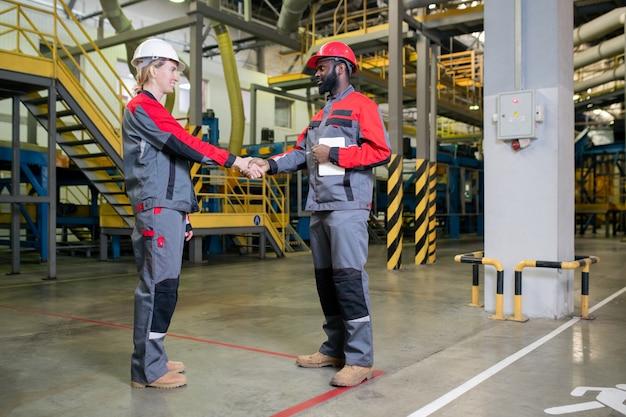 Fabrikarbeiter begrüßen sich gegenseitig