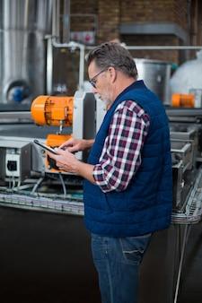 Fabrikarbeiter, der an digitalem tablett in der fabrik arbeitet