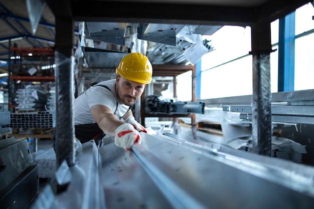 Fabrikarbeiter, der im lager arbeitet, das metallmaterial für die produktion handhabt