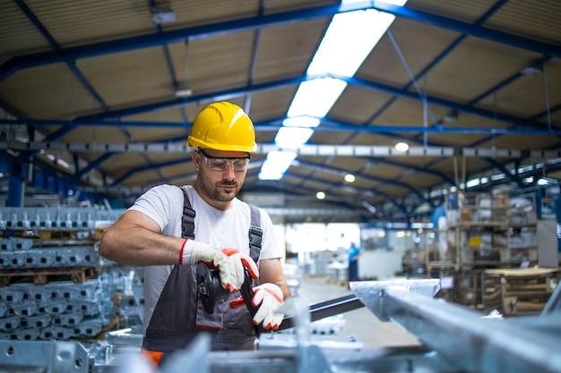Fabrikarbeiter, der in der industriellen produktionshalle arbeitet