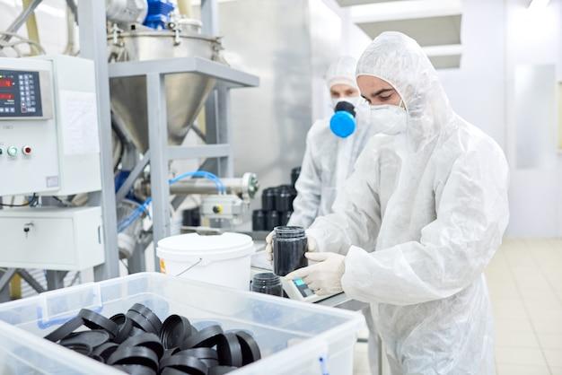 Fabrikarbeiter, der kunststoffbehälter mit produkt trägt