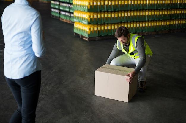 Fabrikarbeiter, der pappkartons in der fabrik aufnimmt