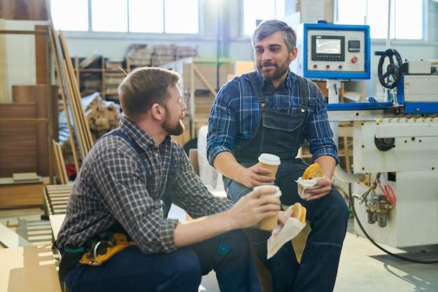 Fabrikarbeiter, die am arbeitsplatz pause machen