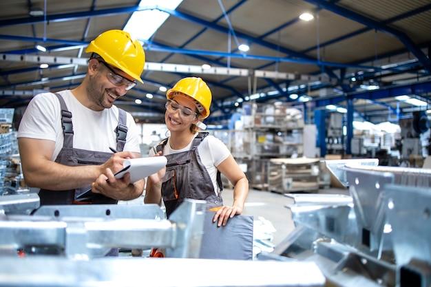 Fabrikarbeiter, die die qualität der produkte in der großen industriehalle überprüfen