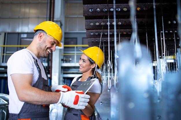 Fabrikarbeiter, die in der halle der industriemetallproduktionslinie zusammenarbeiten