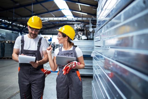 Fabrikarbeiter, die in der industriellen produktionshalle zusammenarbeiten