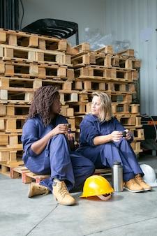 Fabrikarbeiter, die plaudern, während sie kaffee trinken, kekse essen, auf holzpalette im lager sitzen