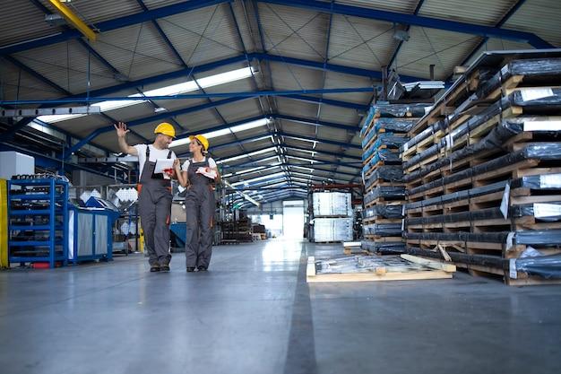 Fabrikarbeiter in arbeitskleidung und gelben helmen gehen durch die industrieproduktionshalle und tauschen ideen über die organisation aus