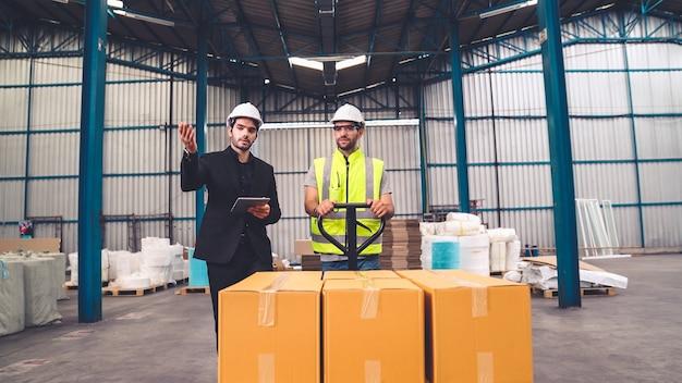 Fabrikarbeiter liefern kistenpakete auf einem schubwagen im lager.