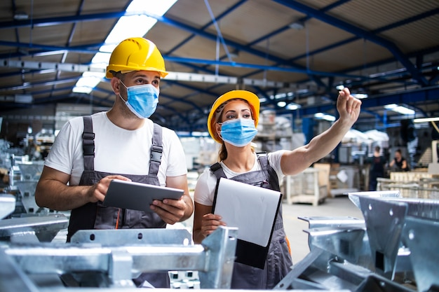 Fabrikarbeiter mit gegen das koronavirus geschützten gesichtsmasken führen eine qualitätskontrolle der produktion in der fabrik durch