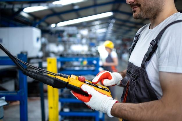 Fabrikarbeiter mit uniform und helm, der die industriemaschine mit druckknopf-joystick in der produktionshalle bedient