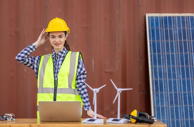 Fabrikarbeiter oder ingenieure, die eine glühbirne halten und einen tablet-computer mit windmühle verwenden