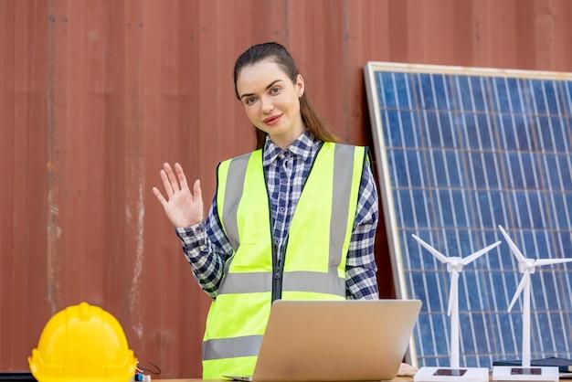 Fabrikarbeiter oder ingenieure, die eine glühbirne halten und einen tablet-computer mit windmühlenmodell verwenden
