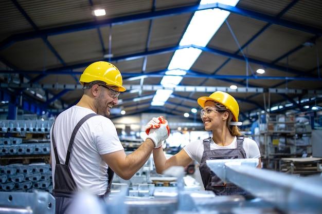Fabrikarbeiter schütteln sich gegenseitig an der produktionslinie