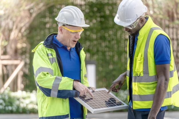 Fabrikarbeiter techniker ingenieur männer überprüfen solarzellen-panel auf nachhaltige technologie mit grünem arbeitsanzug kleid und schutzhelm.