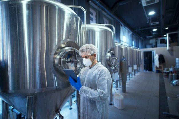 Fabrikarbeiter-technologe in schutzuniform mit haarnetz und maske, die lebensmittelproduktion auf tablet-computer steuern