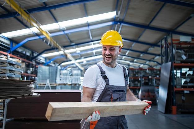 Fabrikarbeiter zimmermann hält holzmaterial und arbeitet in der möbelindustrie