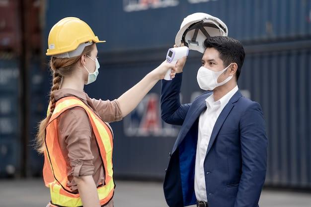 Fabrikarbeiterin in einer gesichtsmaske und einem verwendeten sicherheitskleid misst die temperatur