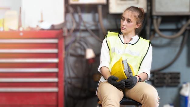 Fabrikarbeiterin mit schutzhelm
