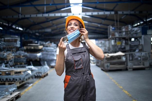 Fabrikarbeiterin setzt eine hygienemaske auf das gesicht, um sich vor hoch ansteckendem koronavirus zu schützen