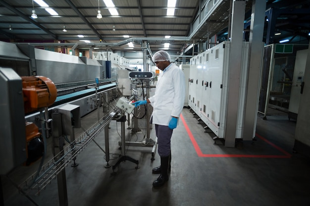 Fabrikingenieur, der die maschine im werk bedient