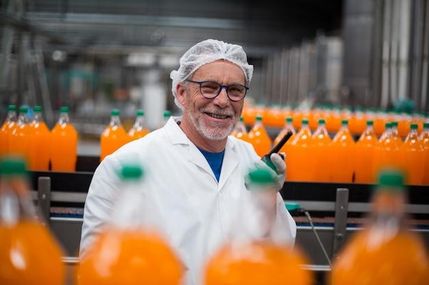 Fabrikingenieur, der nahe der produktionslinie mit walkie-talkie steht