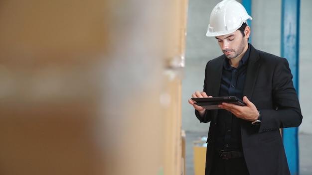 Fabrikmanager mit tablet-computer im lager oder in der fabrik. industrie- und supply-chain-management-konzept.