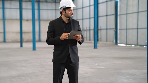 Fabrikmanager mit tablet-computer im lager oder in der fabrik. industrie- und supply-chain-management-konzept.