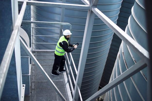 Fabriksilosarbeiter, der auf metallplattform zwischen industriellen lagertanks steht und tablette über lebensmittelproduktion betrachtet