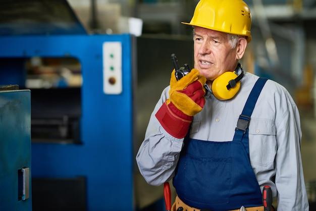 Fabrikvorarbeiter, der durch funkgerät spricht