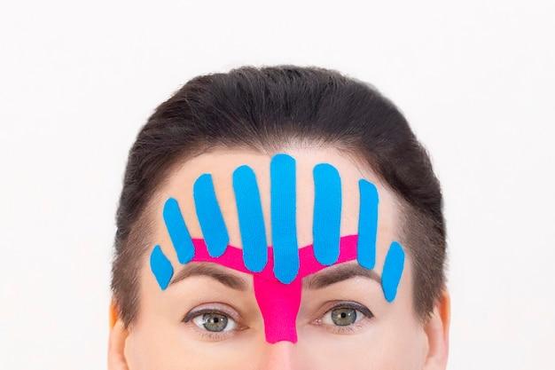 Face taping, nahaufnahme eines mädchengesichts mit kosmetologischem anti-falten-tape. gesichtsästhetisches taping. nicht-invasive anti-aging-hebemethode zur reduzierung von falten