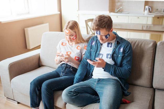 Facebook-symbol. junger mann und junge frau sind von sozialen medien abhängig. konzept der suchtgefahr von laptops smartphones. auf dem sofa sitzen.