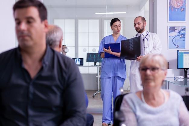 Facharzt, der patientenröntgen hält und der krankenschwester die krankheitsdiagnose erklärt, während sie im wartebereich des krankenhauses steht. behinderte ältere frau im rollstuhl, die auf ärztliche untersuchung wartet