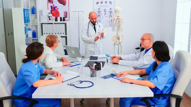 Facharzt, der radiographie während des medizinischen seminars für medizinisches personal im konferenzraum unter verwendung des menschlichen skelettmodells hält. kliniktherapeut im gespräch mit kollegen über krankheit, mediziner