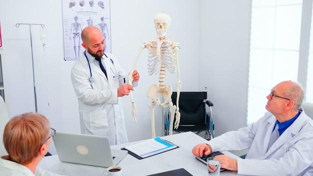 Facharzt für radiologie, der während der präsentation im konferenzraum des krankenhauses auf das menschliche skelett zeigt. kliniktherapeut im gespräch mit kollegen über krankheit, mediziner.