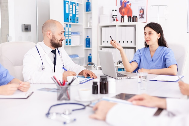 Facharzt im gespräch mit krankenschwester während der diskussion über neue technologien in der medizin. kliniktherapeut mit kollegen, die über krankheit, experten, spezialisten, kommunikation sprechen.