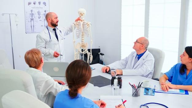 Fachkundiger radiologe, der während des briefings mit medizinischem personal im besprechungsraum des krankenhauses am skelett demonstriert. kliniktherapeut im gespräch mit kollegen über krankheit, mediziner