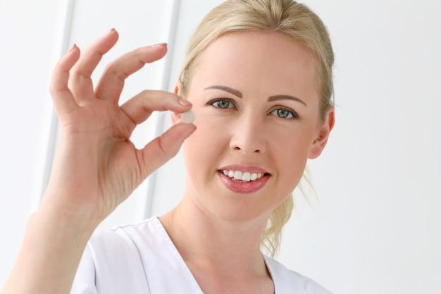 Fachmann. schöne kosmetikerin mit tabletten