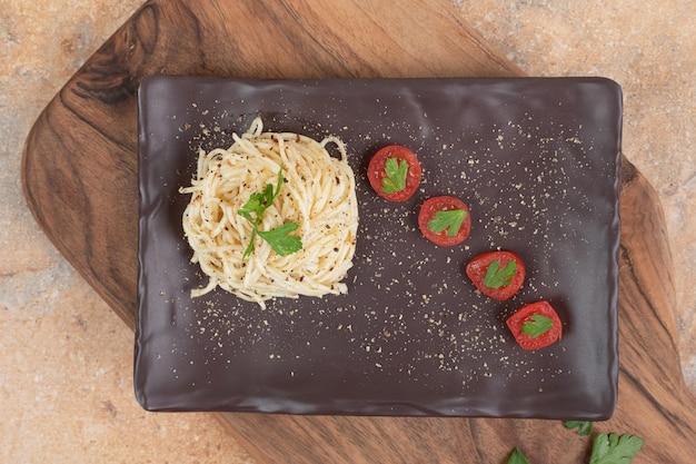 Fadennudeln mit gewürzen und tomaten auf schwarzem teller.