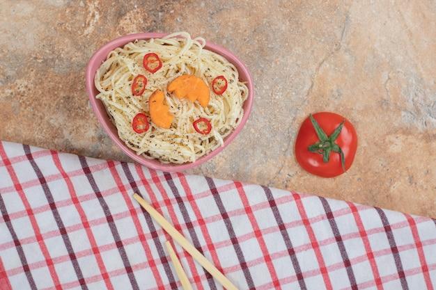 Fadennudeln mit tomaten- und pfefferscheiben auf orangefarbenem hintergrund