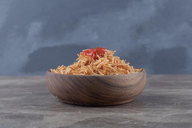 Fadennudeln mit tomatensauce in der schüssel auf der marmoroberfläche.