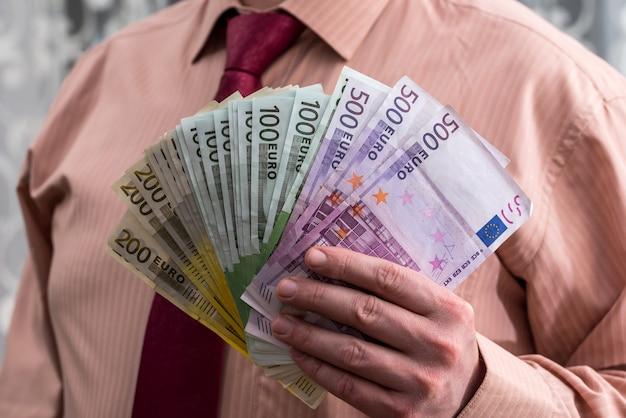 Fächer von euro-banknoten in männlichen händen