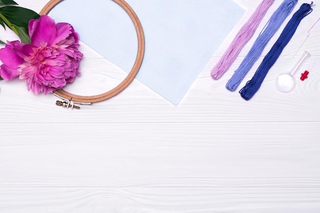 Fäden, ein stickrahmen, eine lupe, eine pfingstrosenblume, eine leinwand auf weiß