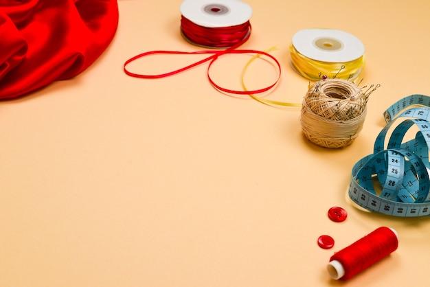 Fäden, knöpfe, roter stoff, maßband. platz kopieren.