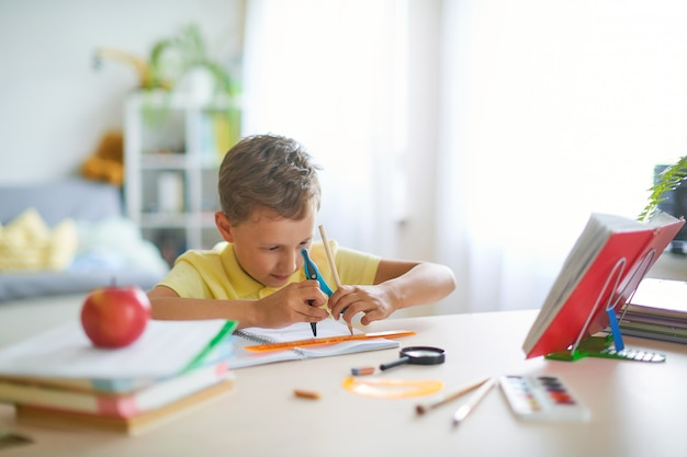 Fähiger junge, der enthusiastisch eine geometrische form mit einem kompasskreis zeichnet.