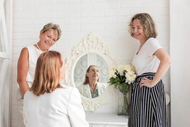 Fällige frau, die mit der tochter betrachtet ihre ältere mutter steht, die vor spiegel sitzt