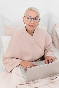 Fällige frau im bett, das an laptop arbeitet
