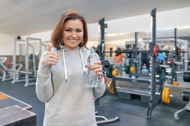 Fällige frau in der gymnastik mit flasche wasser und zeigen des okayzeichens.